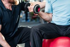 Senior man working out with personal trainer at the gym stock photos