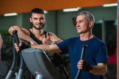Senior man working with personal trainer in gym. Senior men working with personal trainer in gym. Male adult exercising on elliptical machine with assistance of stock images