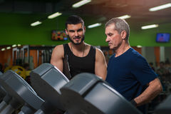 Senior man working with personal trainer in gym. Senior men working with personal trainer in gym. Male adult exercising on treadmill with assistance of fitness stock images