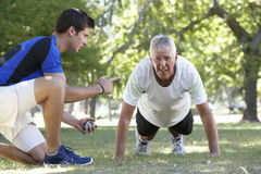 Senior Man Working With Personal Trainer In Park Stock Images