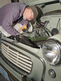 Senior man working on vintage car. Senior man making adjustments to the engine of a vintage car he is restoring Stock Image