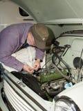 Senior man working on vintage car. Senior man making adjustments to the engine of a vintage car he is restoring Stock Photo