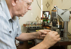 Senior man working at a workbench. Close up side profile of a senior man wearing glasses working at a workbench with small precision tools Stock Images