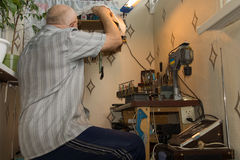 Senior man working at a workbench. Senior man sitting working at a neat workbench turning away from the camera as he reaches for a piece of equipment , low angle Stock Image