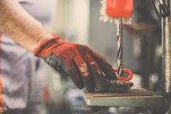 Senior man working in workshop with drill. Royalty Free Stock Image