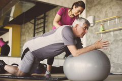 Senior man workout in rehabilitation center. Senior men workout in rehabilitation center. Personal trainer helping senior men on Pilates ball stock photo