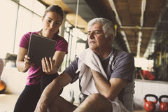 Senior man workout in rehabilitation center. Senior men workout in rehabilitation center. Personal trainer showing something  on digital tablet Royalty Free Stock Photos