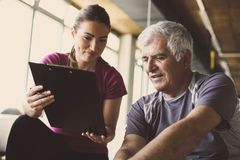 Senior man workout in rehabilitation center. Senior men workout in rehabilitation center. Personal trainer writing record exercise Royalty Free Stock Images