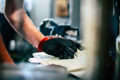 Senior man in workshop. Man writing obligations in his notes. Close up Stock Photography