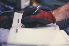 Senior man in workshop. Man writing obligations in his notes. Close up Stock Photo