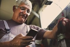 Senior man in workshop using smart phone. Stock Image