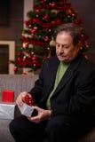 Senior man wrapping christmas gift Stock Images