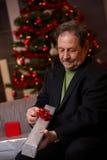 Senior man wrapping christmas present Royalty Free Stock Photo