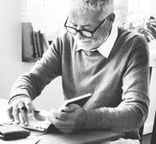 Senior man writing down some notes Stock Photos