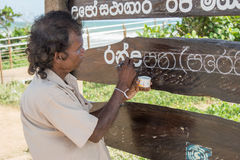 Senior man writing on the public information board. In Sri Lanka Royalty Free Stock Image