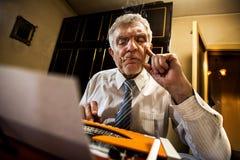 Senior man writing on a typewriter Stock Image