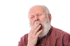 Senior man yawning, isolated on white. Handsome bald and bearded senior man yawning while covering mouth with hand, isolated on white background Stock Image
