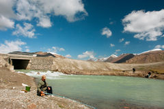 Senior man and young boys fishing in a mountain river with rapid flow under clouds Royalty Free Stock Images