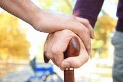 Senior man and young caregiver holding hands Royalty Free Stock Images
