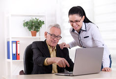 Senior man and young woman looking at laptop Stock Images