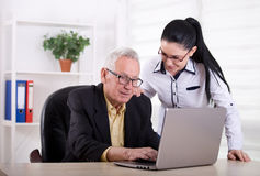Senior man and young woman looking at laptop Stock Photos
