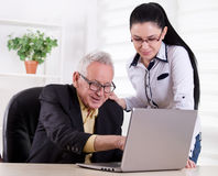 Senior man and young woman looking at laptop Royalty Free Stock Photos
