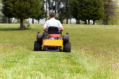 Senior man on zero turn lawn mower on turf royalty free stock images