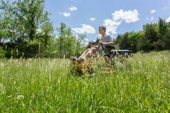 Senior man on zero turn lawnmower in meadow Stock Photo