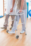 Senior man on zimmer frame with therapist Stock Photos