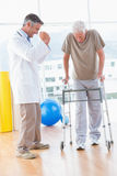 Senior man on zimmer frame with therapist Stock Image