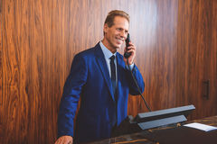 Senior manager answering call in lobby Royalty Free Stock Photography