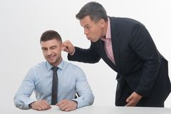 Senior manager chief pulling his employee ear Stock Image