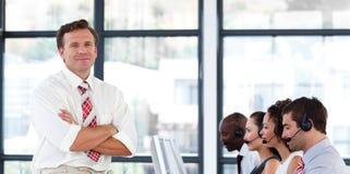 Senior Manager con le braccia piegate in una call center Fotografie Stock Libere da Diritti