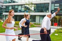 Senior Manager, der einen Lauf mit seinem Geschäftsteam gewinnt Stockfotos