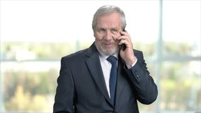 Senior manager talking on mobile phone. Older businessman wearing suit and tie talking on cell phone on office background stock footage