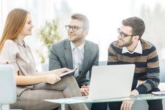 Senior Manager und Mitglieder des Geschäfts team, einen Finanzplan der Firmenentwicklung an dem Arbeitsplatz besprechend Stockfoto