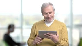 Senior manager using pc tablet. Elderly man with computer tablet on office background. People, technology, lifestyle stock footage