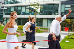 Senior manager winning a run with his business team. Successful senior manager winning a run with his business team at the finish line Stock Photos