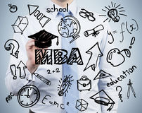 A senior manager is writing down the advantages of the master's degree in business administration. Royalty Free Stock Photography