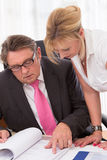 Senior managing director with his secretary at desk Royalty Free Stock Photos