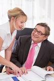 Senior managing director with his secretary at desk Stock Photo