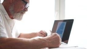 Senior-Mann, der mit Laptop zu Hause arbeitet Alter Mann, der Computer zu Hause benutzt, sitzt auf dem Stuhl und schaut auf den B stock video