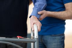 Senior Mans Hands On Walking Frame With Care Worker In Backgrou. Nd Stock Photography