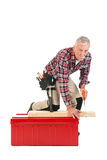 Senior manual worker sawing Royalty Free Stock Photography