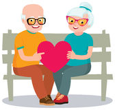 Senior married couple sits on a bench holding a heart symbol Royalty Free Stock Photo