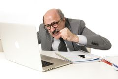 Senior mature busy business man with bald head on his 60s working stressed and frustrated at office computer laptop desk looking a. Ngry and overwhelmed in job Royalty Free Stock Image