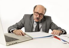 Senior mature busy business man with bald head on his 60s working stressed and frustrated at office computer laptop desk. Looking tired and overwhelmed in job Stock Photo