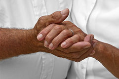 Senior Mature Elderly Couple Holding Hands, Love. Closeup detail of mature senior elderly couple holding hands. A man and woman growing old together does not Stock Photography