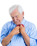 Senior mature, elderly man very nervous, stressed, anxious, thinking about something making him crazy while fumbling with his tie Stock Images