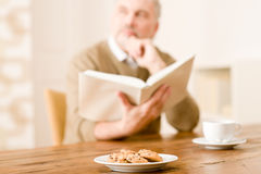 Senior mature man, cookies at wooden table Royalty Free Stock Image